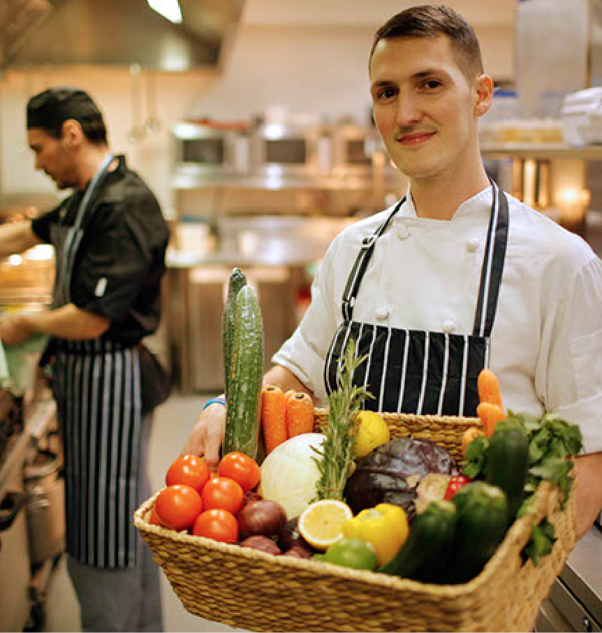 Staff member holding basket of fresh produce